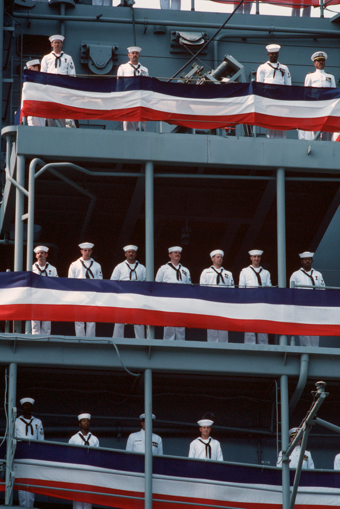 Crewmen man the rails aboard the Amphibious Assault Ship USS WASP (LHD 1) during the vessel's commissioning ceremony.  The first ship in its class, WASP combines flight deck and well deck capabilities with a state-of-the-art combat information center and several newly developed systems