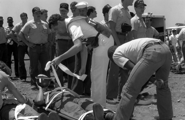 Stretcher bearers stand by as mock casualties are prepared for transport during a mass casualty drill