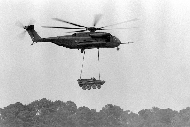 A Ch-53E Super Stallion helicopter airlifts a light assault vehicle (LAV) during a demonstration