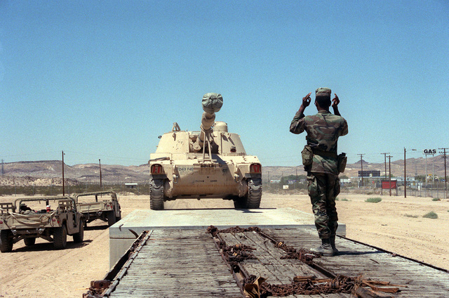 A soldier of the 24th Infantry Division (Mechanized) guides an M-109 155mm self-propelled howitzer onto a flatcar at the Yermo railroad yard following the unit's rotation to the National Training Center at Fort Irwin. Exact Date Shot Unknown