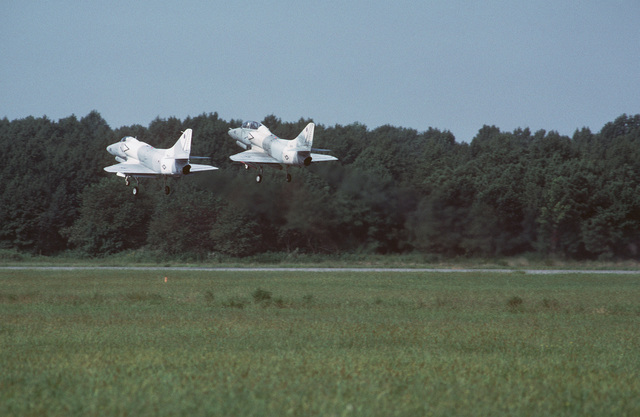 A TA-4J Skyhawk aircraft and an A-4E Skyhawk aircraft, both of Fighter Squadron 43 (VF-43), take off