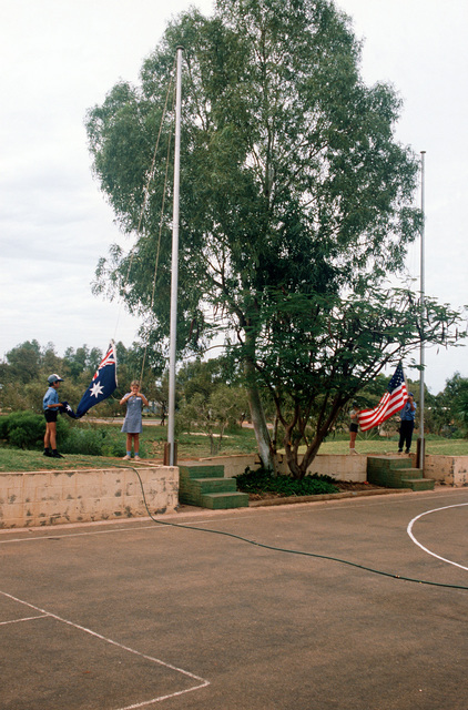 Australian and American children raise the flags of both countries at their joint school. Their parents are stationed at the US/Australian Naval Communications Station Harold E. Holt