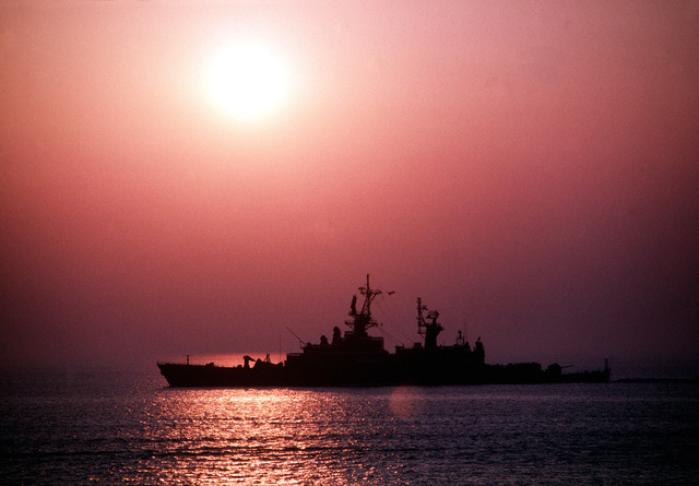 The guided missile cruiser USS BELKNAP (CG 26) is silhouetted against the setting sun as it makes for the Mediterranean. BELKNAP, scheduled along with the Aegis guided missile cruiser USS THOMAS S. GATES (CG 51) and the guided missile frigate USS KAUFFMAN (FFG 59) for a historic visit to the Soviet Black Sea Fleet Headquarters of Sevastopol, was redeployed after the reported murder of Marine Lieutenant Colonel William R. Higgins in Lebanon