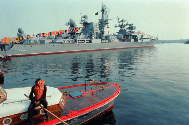 A Soviet Naval infantryman (marine) sits on a small craft. Moored behind it is the Soviet guided missile cruiser AZOV, fully dressed for the goodwill visit of the Aegis guided missile cruiser USS THOMAS S. GATES (CG 51) and the guided missile frigate USS KAUFFMAN (FFG 59). The Americans are making the second such visit by US warships to a Soviet port since World War II. (SUBSTANDARD)