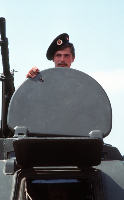 A Soviet naval infantryman (Marine) stands in the open hatch of a Soviet BTR-60PB amphibious armored personnel carrier, with the vehicle's 14.5 mm KPV heavy machine gun next to him