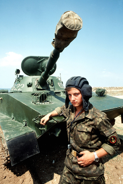 A Soviet naval infantryman (marine) stands with an arm on his PT-76 light amphibious tank, on display for visiting Americans. The Aegis guided missile cruiser USS THOMAS S. GATES (CG 51) and the guided missile frigate USS KAUFFMAN (FFG 59) are making the second goodwil visit to a Soviet port by American warships since World War II
