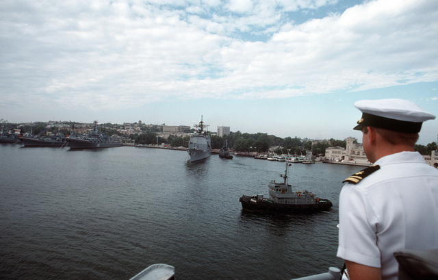 An American officer looks past a harbor tug to the Aegis Guided Missile Cruiser USS THOMAS S. GATES (CG 51), anchored in the harbor along with a line of Soviet warships.  GATES and the Guided Missile Frigate USS KAUFFMAN (FFG 59 are making the second goodwill visit to a Soviet port by American warships since World War II