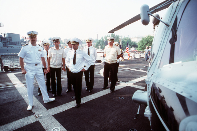 An American officer shows a group of Soviet admirals and their aides an SH-60B Sea Hawk helicopter.  The Aegis guided missile cruiser USS THOMAS S. GATES (CG 51) and the guided missile frigate USS KAUFFMAN (FFG 59) are making the second goodwill visit to a Soviet port by American warships since World War II