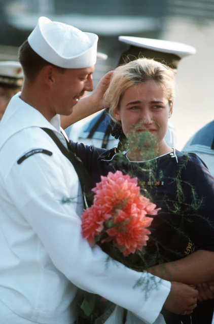 An American Sailor says good-bye to a young Soviet woman with a bouquet.  The Aegis guided missile cruiser USS THOMAS S. GATES (CG 51) and the guided missile frigate USS KAUFFMAN (FFG 59) are making the second goodwill visit to a Soviet port by American warships since World War II