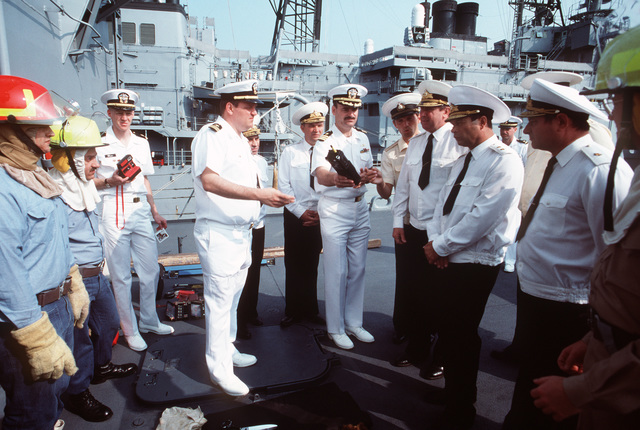 Soviet officers touring the Aegis guided missile cruiser USS THOMAS S. GATES (CG 51) are shown a walkie-talkie and exhibits of shipboard operations.  GATES and the guided missile frigate USS KAUFFMAN (FFG 59) are making the second goodwill visit to a Soviet port by American warships since World War II