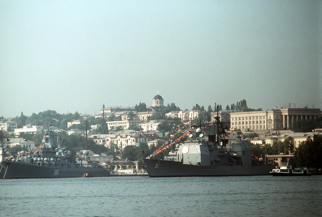 The Aegis guided missile cruiser USS THOMAS S. GATES (CG 51) and the Soviet guided missile cruiser SLAVA lie at anchor in the harbor. Gates and the guided missile frigate USS KAUFFMAN (FFG 59) are making the second goodwill visit to a Soviet port since World War II