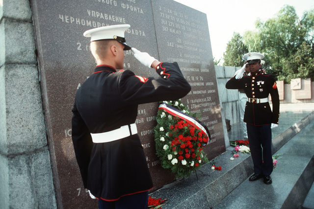 Two US Marines salute after laying a wreath at the monument for the port's war heroes. The Aegis guided missile cruiser USS THOMAS S. GATES (CG 51) and the guided missile frigate USS KAUFFMAN (FFG 59) are making the second goodwill visit by American warships to a Soviet port since World War II