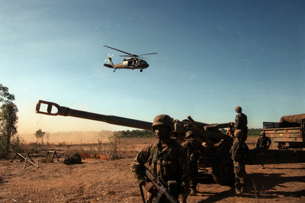 A UH-60 Black Hawk helicopter passes overhead as artillery operating in support of soldiers from 4th Bn., 87th Inf., 25th Inf. Div. (Light), set up their M-198 155mm howitzer during the joint Australian/U.S. exercise Kangaroo '89
