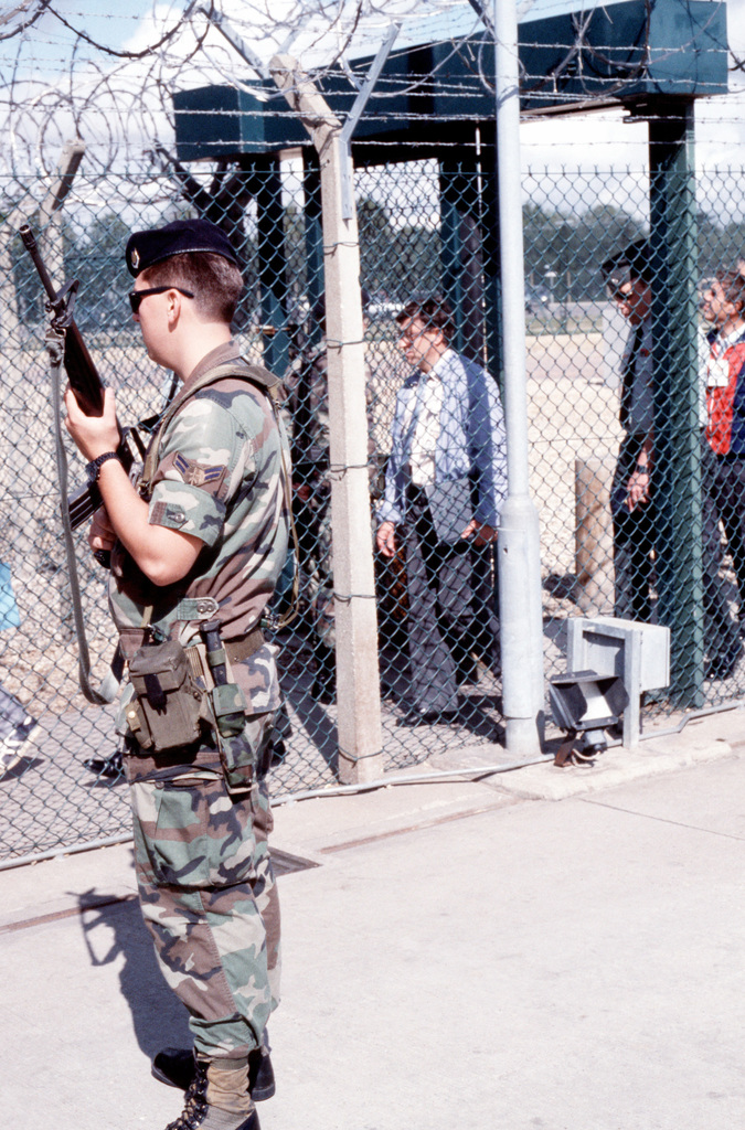 An Air Force sentry armed with an M-16A1 rifle stands at the gate of a weapons storage area on the base as a Soviet inspection team is processed into the compound. The team will be checking the site to ensure NATO compliance with the terms of the Intermediate Range Nuclear Forces (INF) Treaty