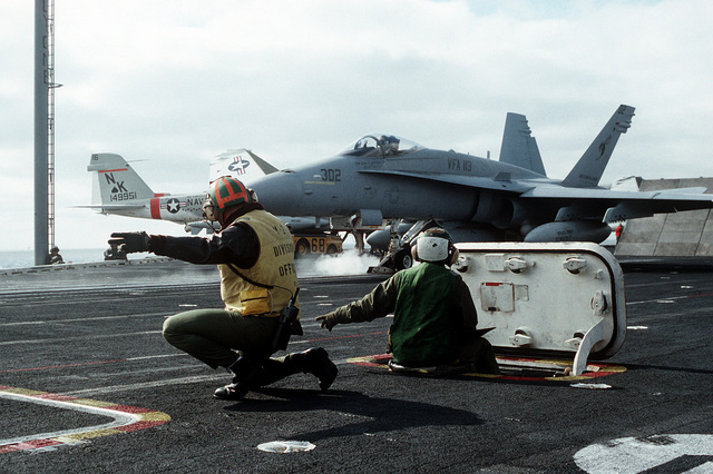A catapult officer signals for the launch of a Strike Fighter Squadron 113 (VFA-113) F/A-18A Hornet aircraft from the flight deck of the aircraft carrier USS Constellation (CV-64) during PACEX '89