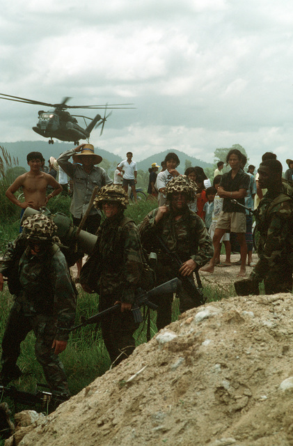 A CH-53E Super Stallion helicopter flies over members of the local population and members of the 11th Marine Expeditionary unit working their way inland during the joint Thai/US exercise THALAY THAI '89