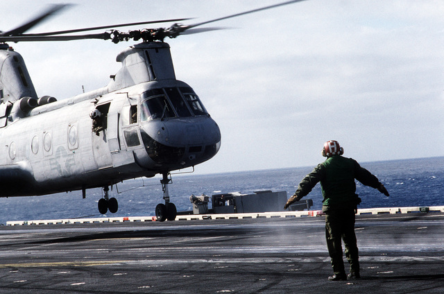 A flight deck crew member signals to the pilot as a CH-46 Sea Knight helicopter lands aboard the aircraft carrier USS CONSTELLATION (CV 64) during PACEX '89