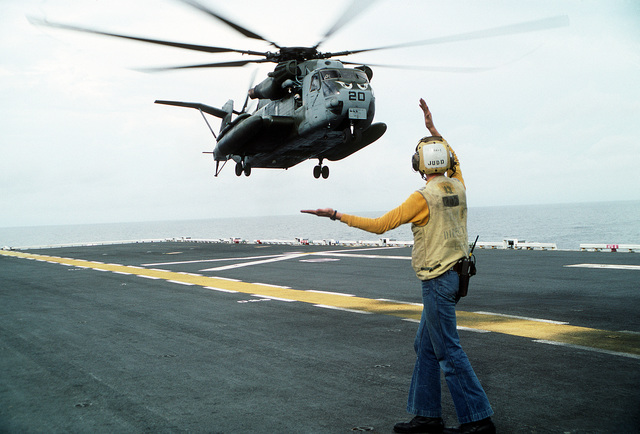 A flight deck director aboard the amphibious assault ship USS TARAWA (LHA-1) guides in a CH-53E Super Stallion helicopter during the combined Thai/U.S. joint Exercise Thalay Thai '89. The helicopter is assigned to Marine Medium Helicopter Squadron 163 (HMM-163), the reinforced aviation combat element of the 11th Marine Expeditionary Unit (11th MEU)
