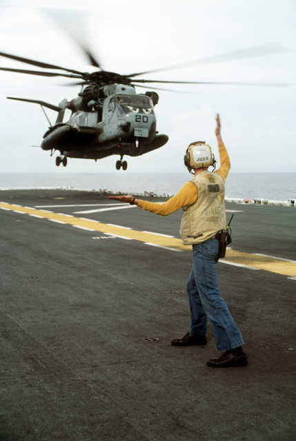 A flight deck director aboard the amphibious assault ship USS TARAWA (LHA-1) guides in a CH-53E Super Stallion helicopter during the combined Thai/U.S. joint exercise Thalay Thai '89. The helicopter is from Marine Medium Helicopter Squadron 163 (HMM-163), the reinforced aviation combat element of the 11th Marine Expeditionary Unit (11th MEU)