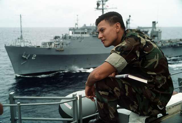 A Marine of the 11th Marine Expeditionary Unit (11th MEU) sits on the edge of the flight deck of the amphibious assault ship USS TARAWA (LHA-1) during the combined Thai/U.S. joint exercise Thalay Thai '89. In the background is the amphibious transport dock USS VANCOUVER (LPD-2)