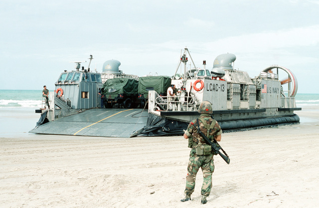 A Marine of the 11th Marine Expeditionary Unit, an M16A2 rifle on his back, prepares to monitor the unloading of air cushion landing craft LCAC13 during the initial assault phase of the joint Thai/US exercise THALAY THAI '89