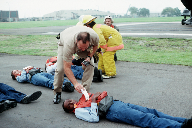 A master-at-arms checks a patients injury tag during a medical evacuation exercise, part of PACEX '89
