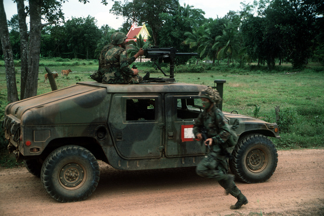 A member of the 11th Marine Expeditionary Unit (11th MEU) runs past two other Marines manning a Mark 19 automatic grenade launcher mounted atop an M-998 high-mobility multipurpose wheeled vehicle (HMMWV) during the combined Thai/U.S. joint exercise Thalay Thai '89