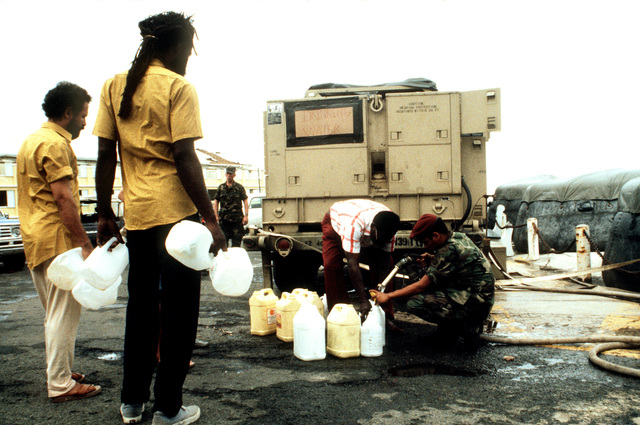 A member of the 82nd Airborne Division provide potable water for local residents during Operation HAWKEYE, a relief effort designed to aid the victims of Hurricane Hugo, which devastated the area on September 19th