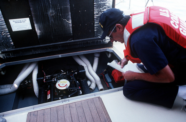 A member of the U.S. Coast Guard inspects the engine compartment of a private cruiser for contraband during a drug interdiction exercise, part of PACEX '89