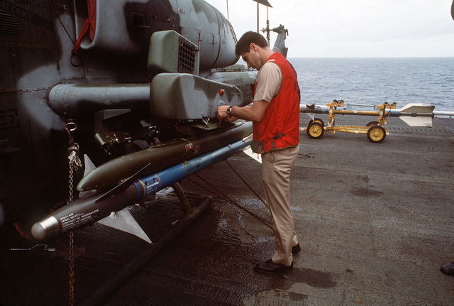 A Navy ordnance officer checks over an AIM-9 Sidewinder missile mounted on an AH-1W Sea Cobra helicopter on the flight deck of the amphibious assault ship USS Tarawa (LHA-1) during the combined Thai/U.S. joint exercise Thalay Thai '89. The helicopter is assigned to Marine Medium Helicopter Squadron 163 (HMM-163), the reinforced aviation combat element of the 11th Marine Expeditionary Unit (11th MEU)