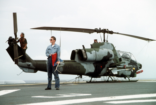 A sailor stands on the flight deck of the amphibious assault ship USS TARAWA (LHA-1) near an AH-1W Sea Cobra helicopter armed with an AIM-9 Sidewinder missile during the combined Thai/U.S. joint exercise Thalay Thai '89. The helicopter is assigned to Marine Medium Helicopter Squadron 163 (HMM-163), the reinforced aviation combat element of the 11th Marine Expeditionary Unit (11th MEU)