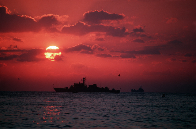 A US Navy ship is silhouetted on the horizon at sunset during the joint Thai/US combined exercise THALAY THAI '89