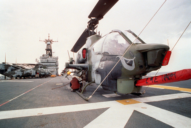 An AH-1W Sea Cobra helicopter armed with an AIM-9 Sidewinder missile, foreground, and several CH-46E Sea Knight helicopters sit on the flight deck of the amphibious assault ship USS TARAWA (LHA-1) during the combined Thai/U.S. joint exercise Thalay Thai '89. The helicopters are assigned to Marine Medium Helicopter Squadron 163 (HMM-163), the reinforced aviation combat element of the 11th Marine Expeditionary Unit (11th MEU)