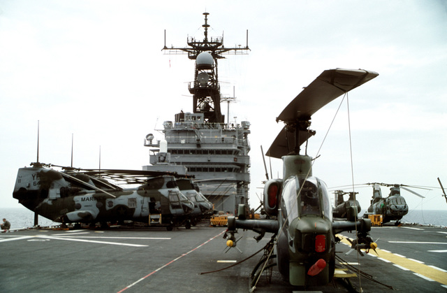 An AH-1W Sea Cobra helicopter armed with two AIM-9 Sidewinder missiles, foreground, and several CH-46E Sea Knight helicopters sit on the flight deck of the amphibious assault ship USS TARAWA (LHA-1) during the combined Thai/U.S. joint exercise Thalay Thai '89. The helicopters are assigned to Marine Medium Helicopter Squadron 163 (HMM-163), the reinforced aviation combat element of the 11th Marine Expeditionary Unit (11th MEU)