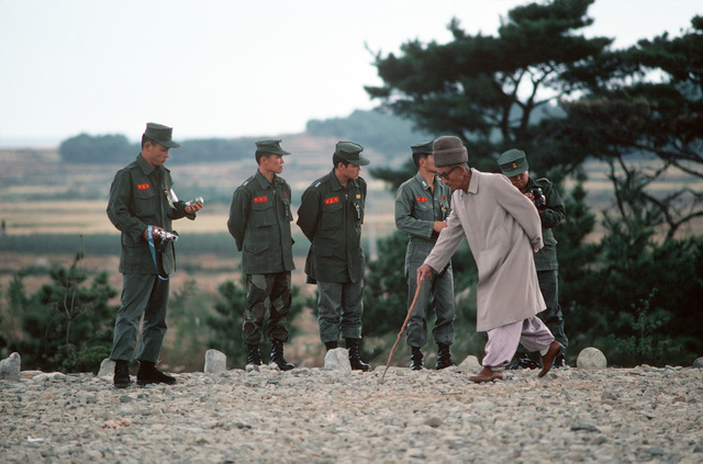 An old man passes Thai army officers gathered to take photographs during the joint Thai/US combined exercise THALAY THAI '89