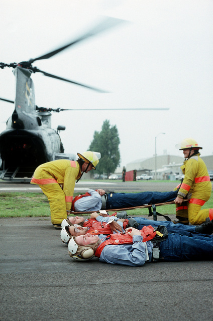 Firefighters prepare to load a patient onto a CH-46 Sea Knight helicopter during a medical evacuation exercise, part of PACEX '89