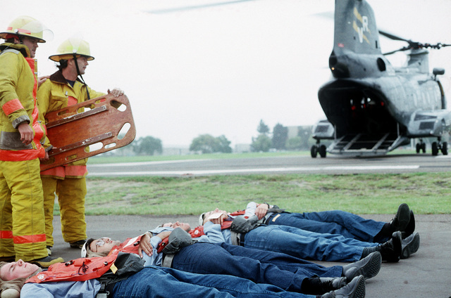 Firefighters prepare to place a patient on a litter during a medical evacuation exercise, part of PACEX '89. The patients are being loaded onto the CH-46 Sea Knight helicopter which is waiting in the background