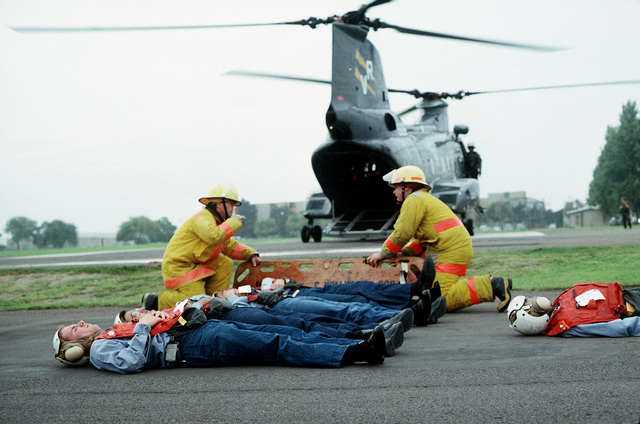 Firefighters prepare to place a patient onto a litter during a medical evacuation exercise, part of PACEX '89. The patients are being loaded onto the CH-46 Sea Knight helicopter which is waiting in the background