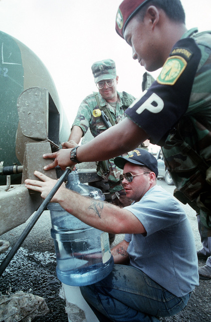 In the wake of Hurricane Hugo, a military disaster relief party, including a sailor from the dock landing ship USS PENSACOLA (LSD 38), draws fresh water from a M106 tank trailer for local residents