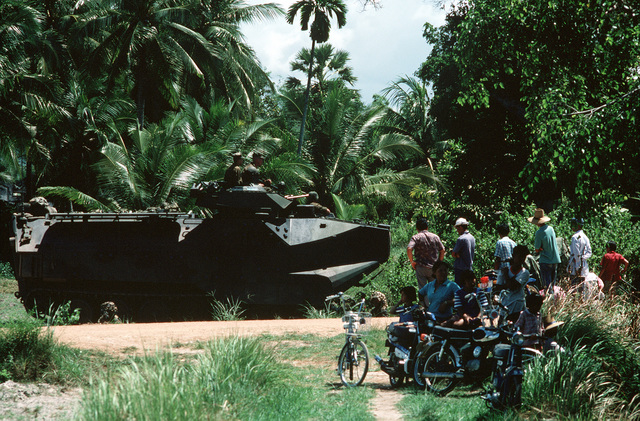 Local inhabitants watch an AAVP7A1 amphibious assault vehicle of the 11th Marine Expeditionary Unit as it moves inland during the joint Thai/US exercise THALAY THAI '89
