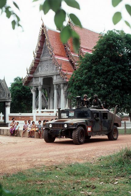 Marines of the 11th Marine Expeditionary Unit (11th MEU) man a Mark 19 automatic grenade launcher mounted atop an M-998 high-mobility multipurpose wheeled vehicle (HMMWV) parked in a village near Pattaya Beach during the combined Thai/U.S. joint exercise Thalay Thai '89
