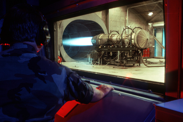 "MASTER SGT. Dick Cochran, 120th Fighter Interceptor Group, Montana Air National Guard, tests an F100-PW-200 jet engine in a facility nicknamed the ""hush house."""