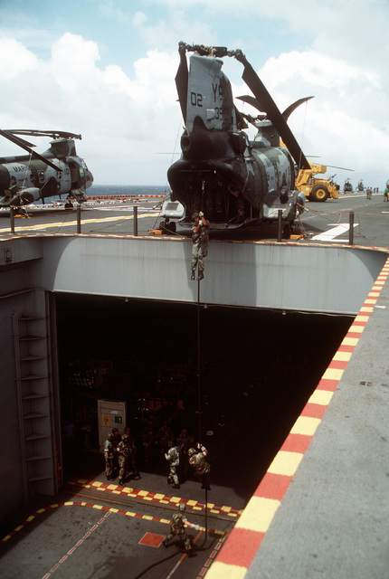 Members of the 11th Marine Expeditionary Unit (11th MEU) practice rope-descending techniques from a CH-46E Sea Knight helicopter positioned at the edge of the stern elevator of the amphibious assault ship USS TARAWA (LHA-1) during the combined Thai/U.S. joint exercise Thalay Thai '89. The helicopter is from Marine Medium Helicopter Squadron 163 (HMM-163), the reinforced aviation combat element of the 11th Marine Expeditionary Unit (11th MEU)