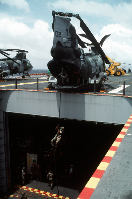 Members of the 11th Marine Expeditionary Unit (11th MEU) practice rope-descending techniques from a CH-46E Sea Knight helicopter positioned at the edge of the stern elevator of the amphibious assault ship USS TARAWA (LHA-1) during the combined Thai/U.S. joint exercise Thalay Thai '89. The helicopter is from Marine Medium Helicopter Squadron 163 (HMM-163), the reinforced aviation combat element of the 11th MEU. Exact Date Shot Unknown
