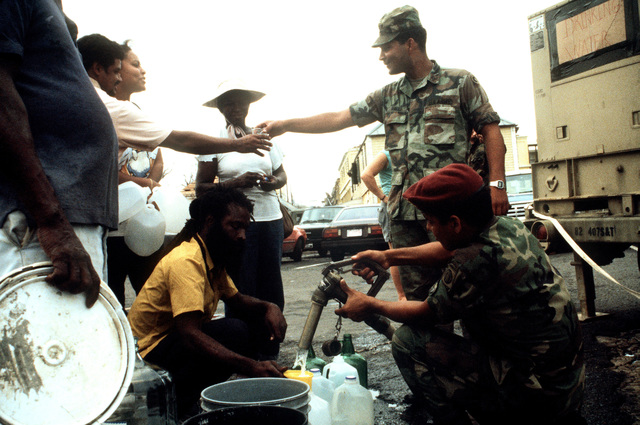 Members of the 82nd Airborne Division provide potable water for local residents during Operation HAWKEYE, a relief effort designed to aid the victims of Hurricane Hugo, which devastated the area on September 19th