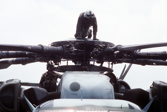 Members of the flight crew of a CH-53E Super Stallion helicopter look over the helicopter's main rotor blades as part of a preflight check aboard the amphibious assault ship USS TARAWA (LHA-1) during the combined Thai/U.S. joint exercise Thalay Thai '89. The helicopter is assigned to , the reinforced aviation combat element of the 11th Marine Expeditionary Unit (11th MEU)