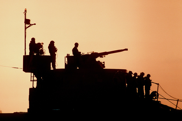 Royal Thai Marines, one manning a Bofors 40mm/60-caliber gun, are silhouetted atop the gun housing on the bow of a Thai tank landing ship during the joint Thai/U.S. combined exercise Thalay Thai '89