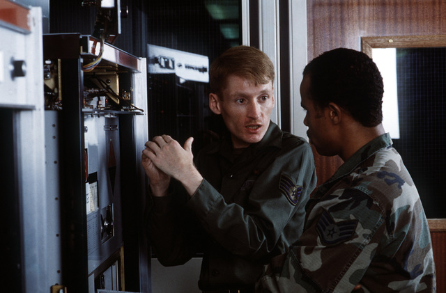 SSGT Charles L. Hendricks, left, a ground radio specialist, and SSGT Glenn E. Cannon, a ground radio technician, discuss maintenance on a 208U-10 linear power amplifier. Both men are members of the 2130th Communications Group (2130th CG), U.S. Air Force Communications Command (AFCC). The 2130th CG operates a high-frequency transmitter and receiver site at Barford St. John