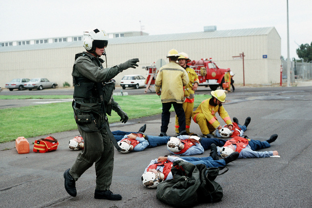 The pilot of a CH-46 Sea Knight helicopter works with firefighters preparing to load patients onto the helicopter during a medical evacuation exercise, part of PACEX '89