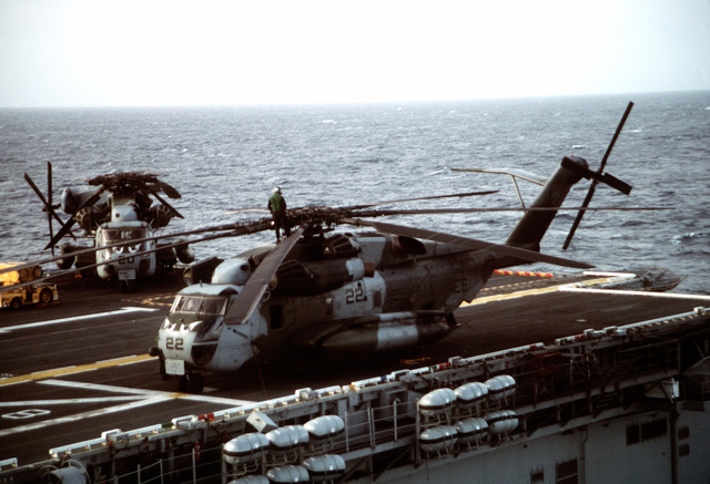 Two CH-53E Super Stallion helicopters sit on the flight deck of the amphibious assault ship USS TARAWA (LHA-1) during the combined Thai/U.S. joint exercise Thalay Thai '89. The helicopters are assigned to Marine Medium Helicopter Squadron 163 (HMM-163), the reinforced aviation combat element of the 11th Marine Expeditionary Unit (11th MEU)